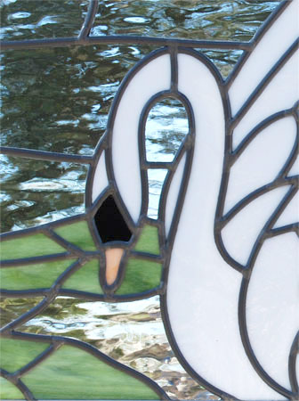 Closeup of custom stained and leaded glass small Swan window