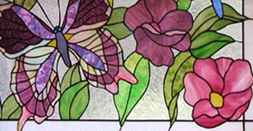 Closeup of stained and leaded glass butterflies and flowers window